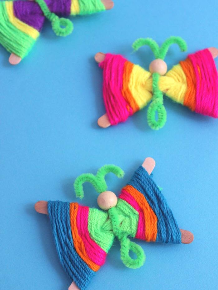 papillons de batonnets de glace décorées de fils de laine et corps en cure pipe et tete en perle de bois, bricolage enfant