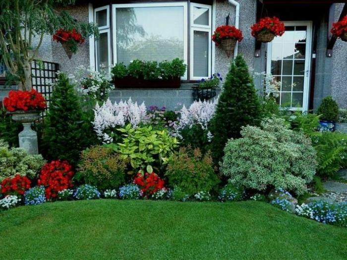 parterre devant maison avec fleurs variées et buies, pelouse verte, maison grise, jardinière à la fenêtre