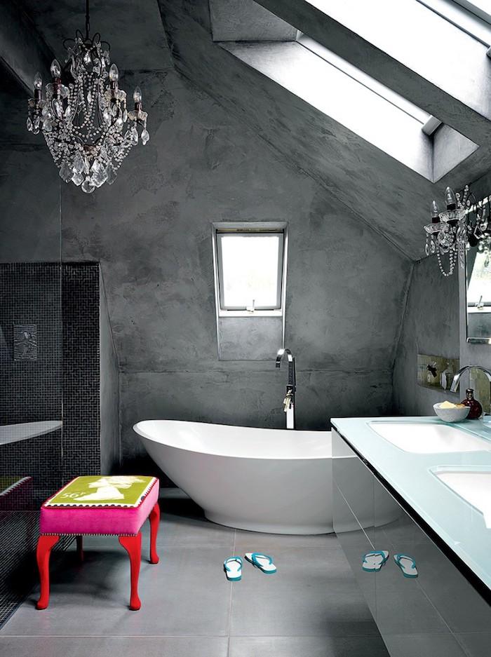 peinture à effet salle de bain à effet béton gris, baignoire blanche, tabouret rose et rouge, sol carrelage gris, lustres élégantes, meuble salle de bain avec plan de travail en verre