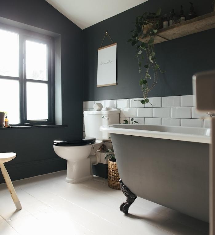 salle de bain aux murs gris anthracite, baignoire à poser grise, soubassement carrelage blanc, parquet blanchi, wc noir et blanc design
