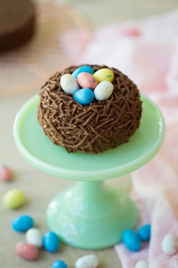 petit gâteau nid de pâques au chocolat garni d'oeufs en chocolat sur un présentoir à gâteaux vert pastel, gâteau classique pour pâques