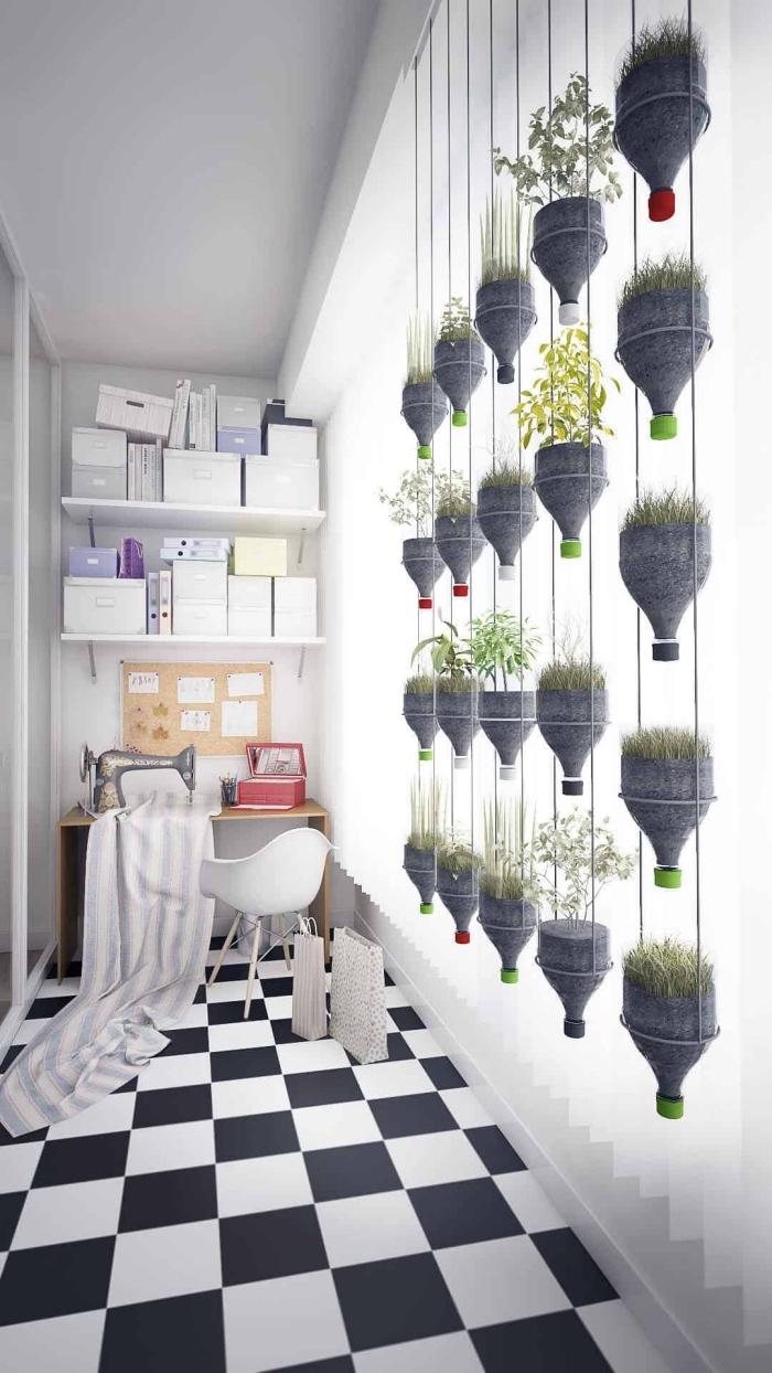 jardin suspendu de bouteilles en plastique recyclées posées en colonnes pour faire pousser des herbes aromatiques et des condiments à l'intérieur de la maison