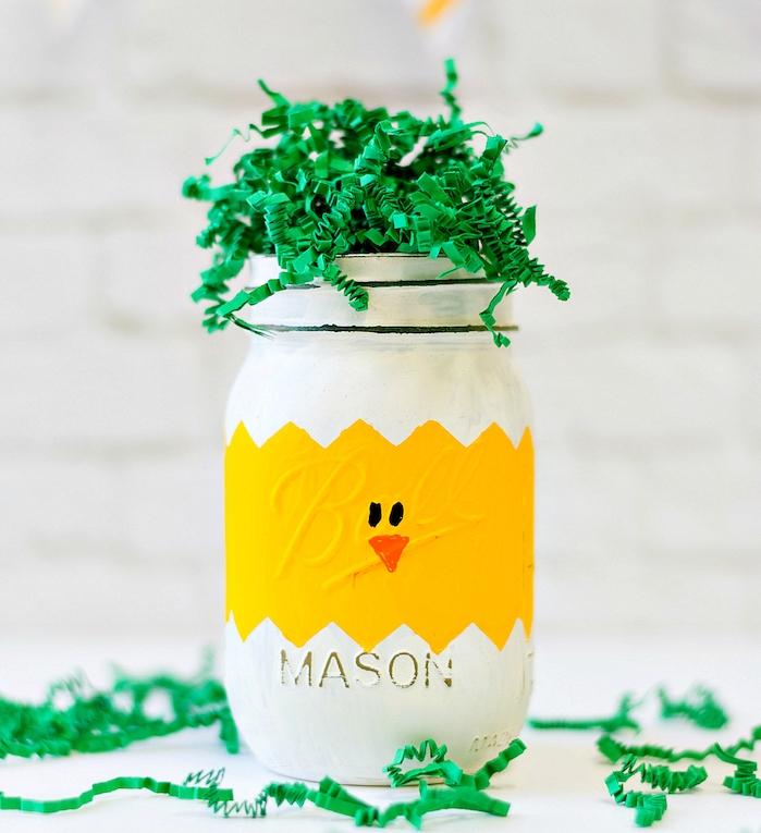 herbe en confettis de papier vermicelles vertes dans un pot en verre repeint de jaune et blanc avec bec et des oreilles dessinés