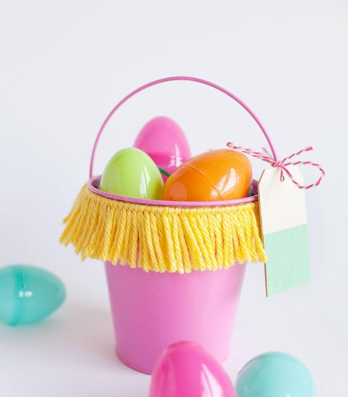 seau décoratif en rose à franges de fils de laine jaunes rempli d oeufs en plastique colorés, decoration paques mignonnes