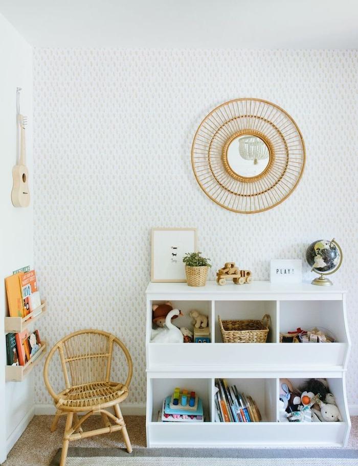 idee de mobilier montessori à cases pour ranger jouets et livres, miroir soleil, chaise tressée bas près d une petite bibliothèque murale