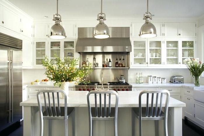 cuisine blanche, chaises grises, lampes chromées, réfrigérateur encastrable, armoires de cuisine vitrées
