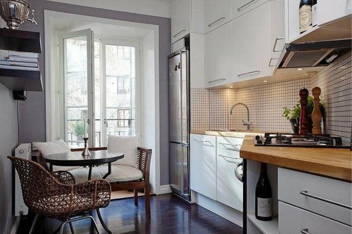 sol en bois foncé, chaise tressée, table bistrot ancienne, armoires suspendues blanches, fenêtre