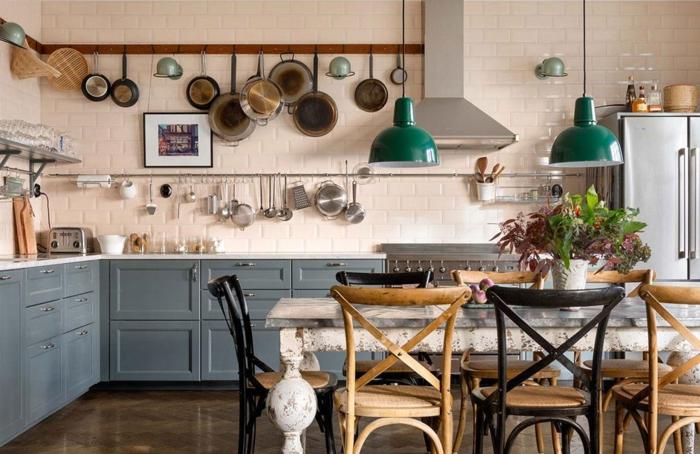 cuisine en beige et bleu, table en marbre, chaises bistrot, poêles suspendues, réfrigérateur en chrome
