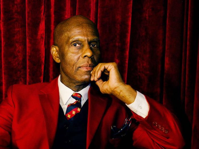 photo de Dapper Dan en costume rouge sur fond velours bordeaux pour article sur sa collaboration Gucci et polémique pull blackface