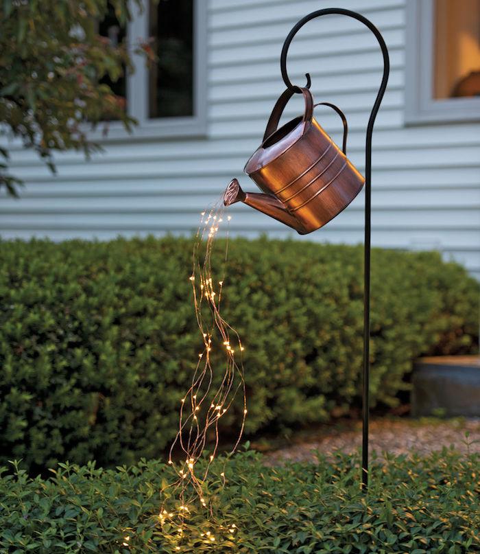 photo d'un arrosoir en cuivre avec fausse coulée d'eau en guirlande lumineuse pour illustrer la douche d'extérieur solaire