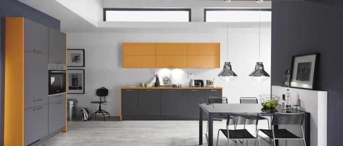 modele de cuisine moderne, déco de cuisine aux murs blancs avec armoires en gris et orange, table à manger gris métallisé