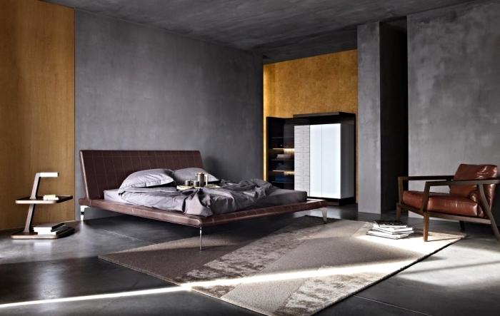 idée comment décorer une chambre masculine aux murs à texture béton, modèle de grand lit avec tête en cuir marron
