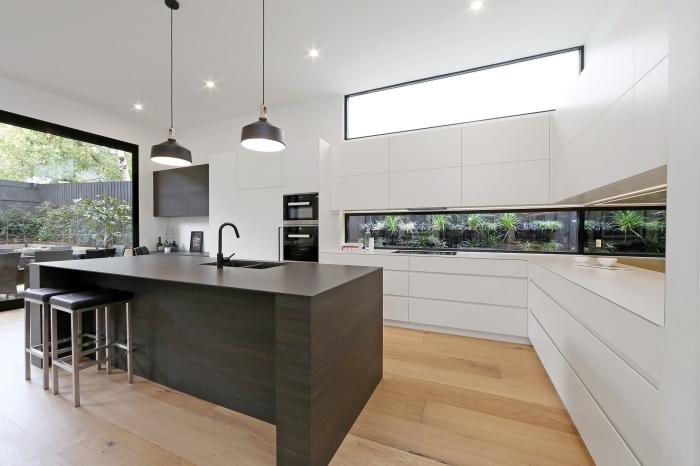 design contemporain et minimaliste dans une cuisine blanche avec crédence aquarium et îlot central en bois gris anthracite