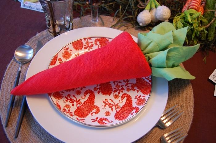 un pliage serviette paques en forme de carotte réalisée avec deux nappes de couleur rouge et verte