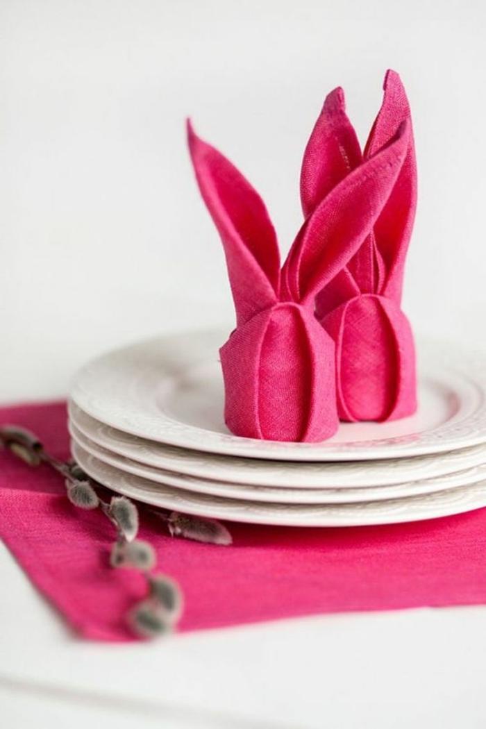 pliage de serviette pour pâques façon lapins arrangés au centre d'une assiette, idée de déco de pâques à faire soi-même