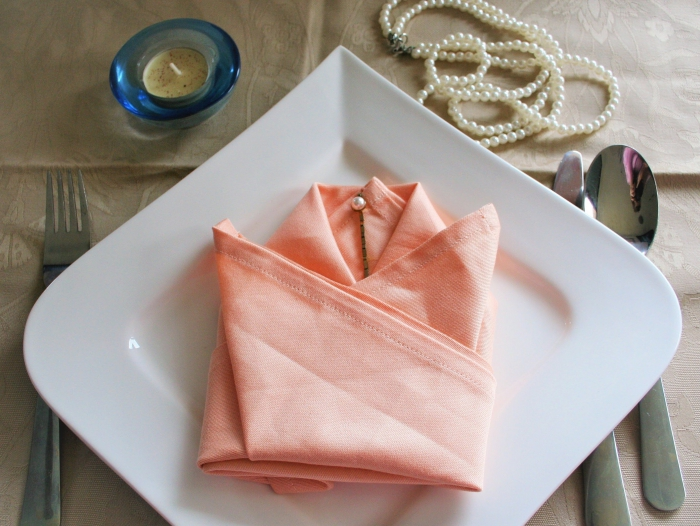déco de table de fête élégante avec une serviette couleur corail pliée en tulipe, idée de pliage serviette paques en forme de fleur