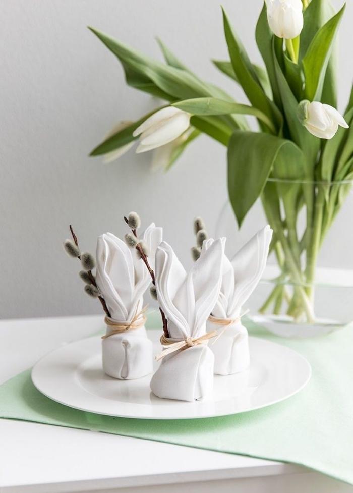 joli pliage de serviette en forme de lapin paques décoré avec des branches naturelles et un joli noeud ruban