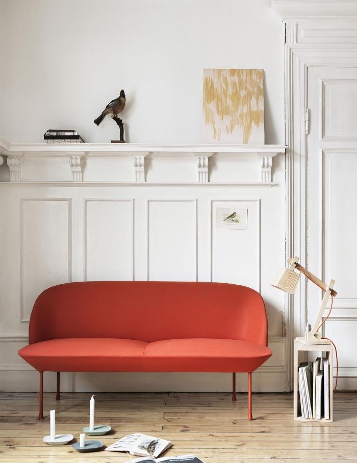 canapé design couleur orange posé contre un soubassement en boiserie murale blanche imitant les éléments architecturaux d'un décor classique