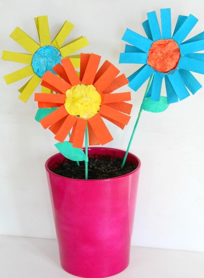 pot de fleurs artificielles en bandes de papier coloré et pot rose rempli de terre avec centre de papier de soie coloré