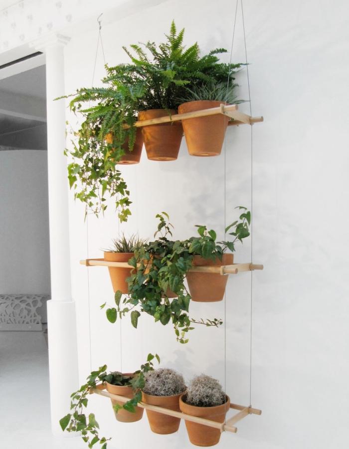un petit jardin vertical de pots d'herbes aromatiques suspendus, des porte-plantes, une suspension pour plantes en pots en structure de bois légère