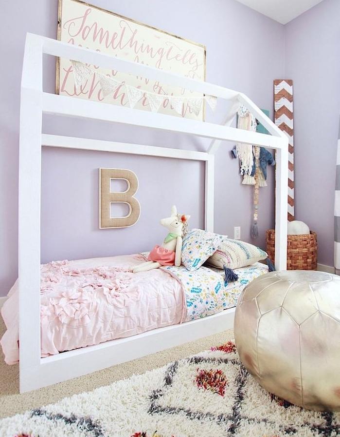 murs couleur violet et lit maisonnette blancs avec linge de lit coloré, tapis noir et blanc, pouf enfant, panier à jouets tressé