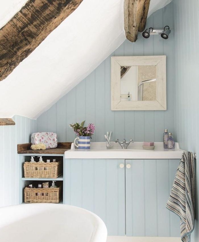 poutres apparentes et lambris repeint en bleu dans une petite salle de bain, baignoire blanche, pente repeinte en blanc