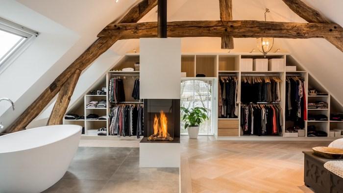 chambre avec salle de bain et ossature en bois, cheminée au centre d une pièce, baignoire blanche sur carrelage gris, grand dressing sous pente