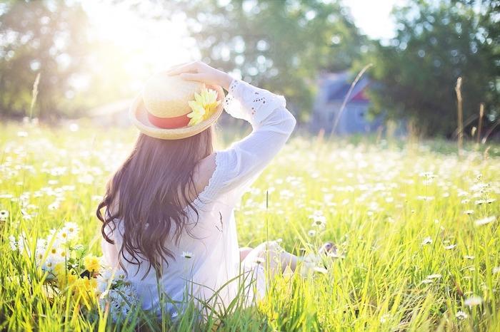 Fille assise sur la peleuse fleurie champ ensoleillé, fille robe blanche et chapeau sur ses cheveux longs, fond d'ecran paysage avec figure de fille en dos, fond ecran fleur, idée d'image à utiliser pour son desktop
