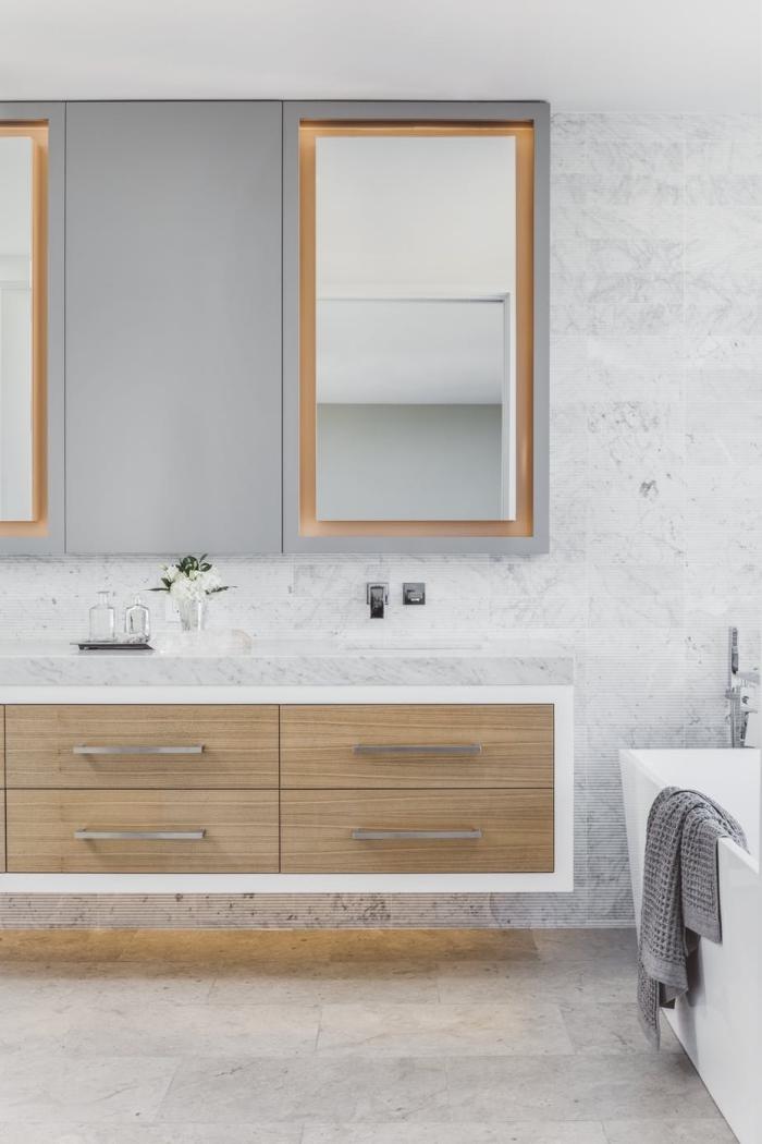 meuble salle de bain en bois avec poignées métal et comptoir blanc, idée carrelage gris clair à effet marbre blanc et gris