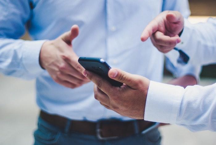 Deux hommes en costumes, mains pointant vers le téléphone portable, les paiements sécurisés