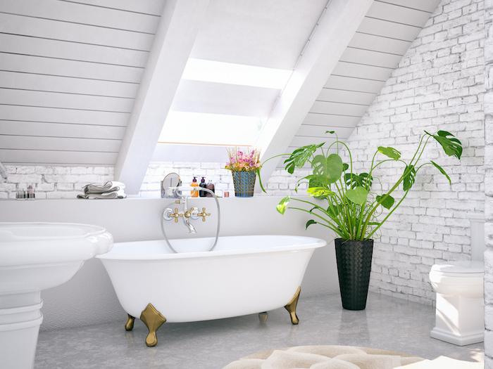 mur de briques, baignoire blanche, plante verte dans pot de fleur, pente poutres bois blanchis, lavabo console, sol gris