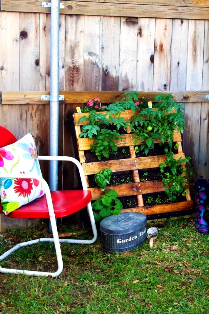 une jardiniere palette avec des plantes aromatiques et des légumes adossée à la clôture, réaliser un potager vertical dans une palette recyclée