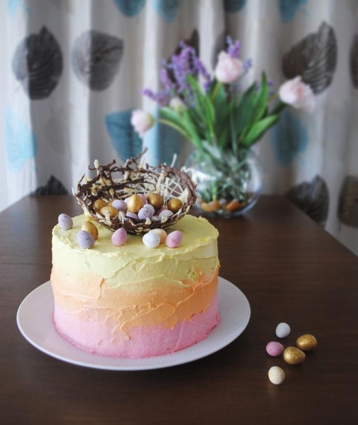 un layer cake nid de paques au glaçage dégradé de crème au beurre rose, orange et jaune avec un nid en chocolat noir et blanc
