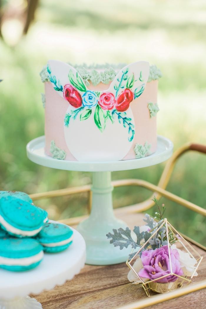 joli layer cake au glaçage lisse rose décoré de petites fleurs réalisées à la poche à douille et d'une tête de lapin en papier