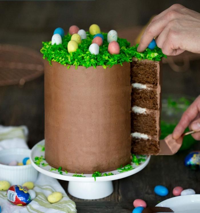 gâteau de pâques à étages au chocolat recouvert de crème au beurre et chocolat lisse et décoré d'herbe de pâques décorative