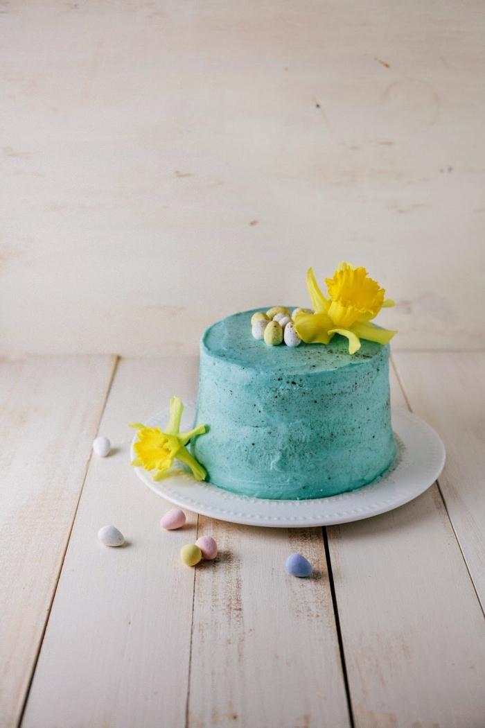 recette de paques pour un gâteau festif au chocolat nappé de crème au beurre coloré bleu turquoise et tacheté décoré de petits œufs en chocolat