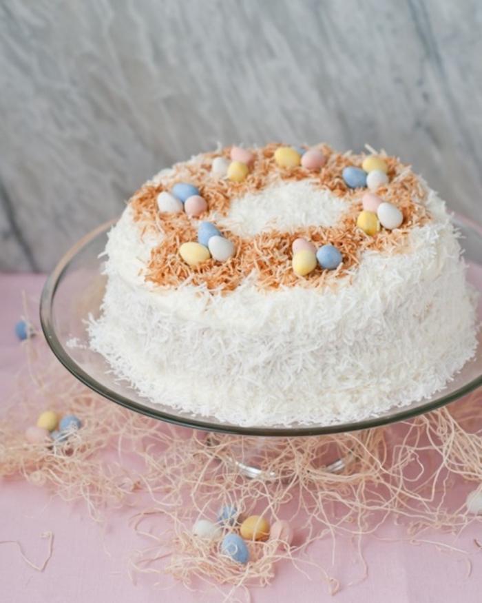 gâteau nid de pâques à la noix de coco décoré de petits oeufs en chocolat en couleurs pastel et de noix de coco grillée