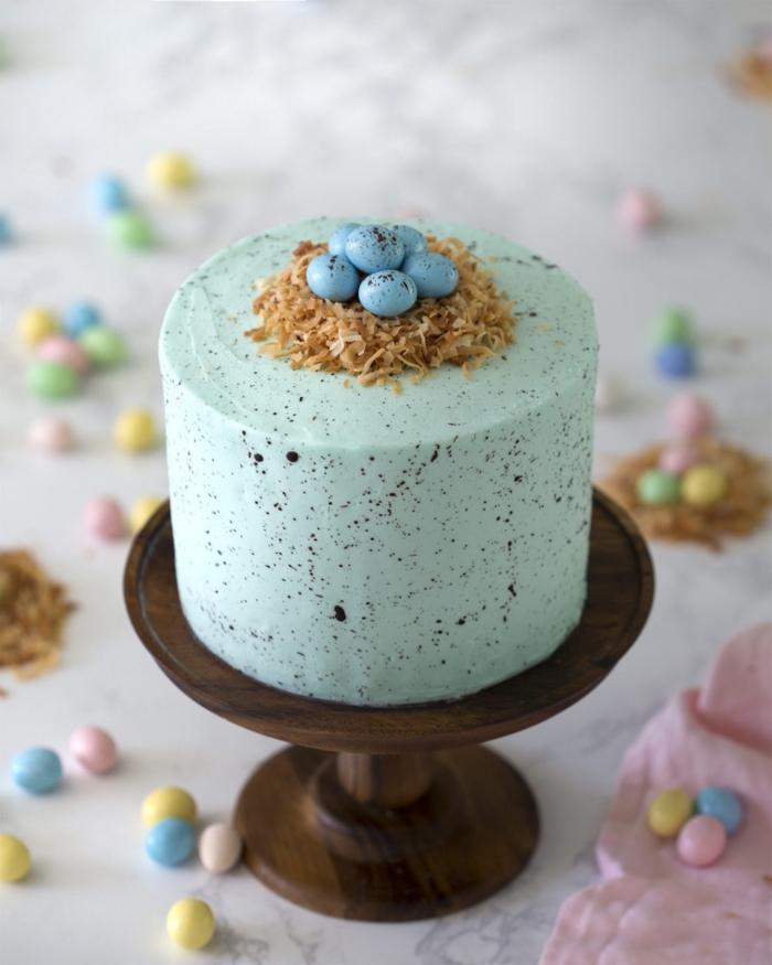 recette facile de gâteau nid de paques vanille recouvert de glaçage crème au beurre teinté vert pastel avec un simple nid en noix de coco