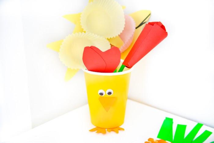 gobelet en plastique poussin aux yeux mobiles et bec de papier rempli de fleurs de papier colorés avec papier simple et caissettes à muffins