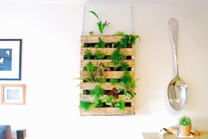 recyclage palette jardinière verticale suspendue au mur intérieur, plantée avec des herbes aromatiques