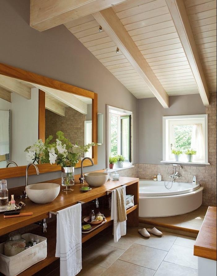 salle de bain bois et gris avec poutres apparentes blanches, carrelage sol beige, meuble salle de bain bois clair, vasque à poser blanc, miroir horizontal, baignoire d angle