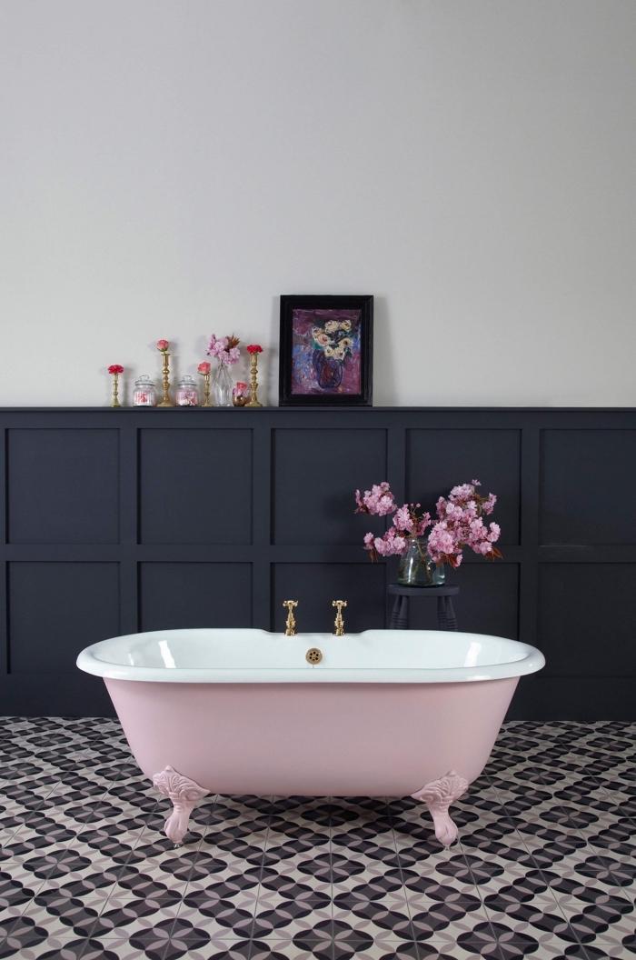 une salle de bains vintage avec un soubassement en panneau mural noir à motifs caissons avec espace rangement en fort contraste avec le mur blanc et la baignoire rose