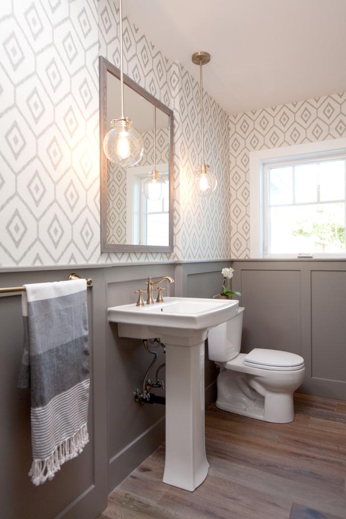 une salle de bains de style campagne chic associant un soubassement en boiserie murale peinte couleur taupe avec du papier peint graphique et vintage sur la partie haute du mur