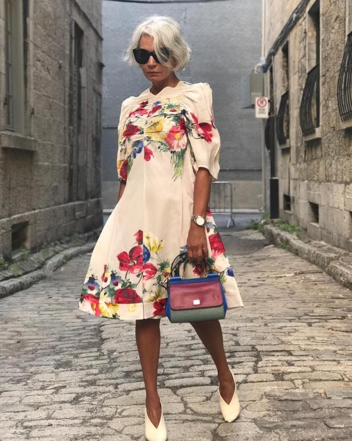 une robe champetre aux imprimés floraux pour une tenue de mariage chic et semi-officielle associée avec un petit sac à main couleur rouge, vert et bleu