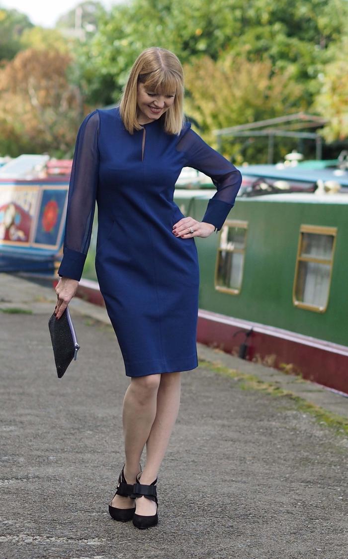 une robe de soirée manche longue transparente de couleur bleu roi, robe de cocktail courte de coupe droite avec une petite fente au niveau du buste