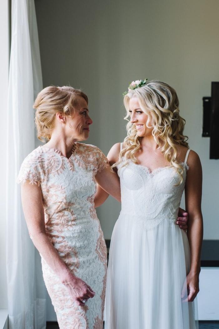 la mère de la mariée dans une robe droite chic avec des appliques en dentelle blanc et beige aux manches courtes