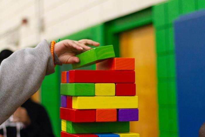 Comment peur un robot apprend à jouer à Jenga, enfant et ses briques colorés, main d'enfant qui pose une pièce de Jenga