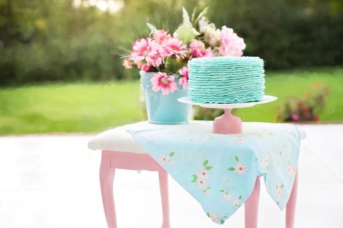 un joli ruffle cake bleu clair au glaçage en rubans pour une fête d'anniversaire sur thème champêtre