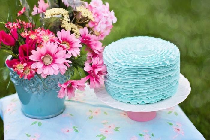 un joli ruffle cake bleu clair au glaçage en rubans posé sur une table de fête couverte de nappe à motifs floraux