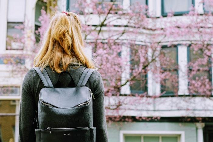 Fille blonde avec sac à dos cuir, photo printemps dans la ville, batiments et arbres fleuries, fantastique fond d'ecran,